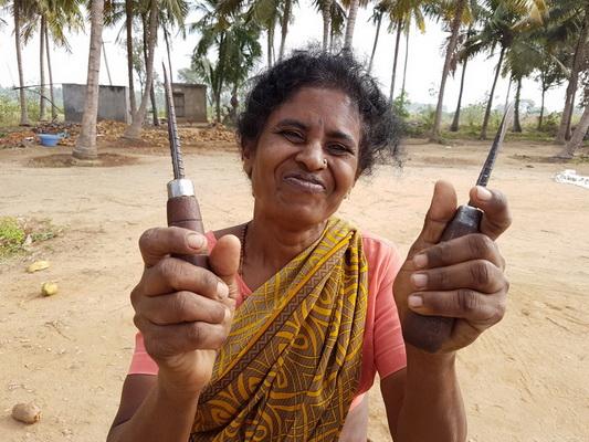 היא מפקחת, בחום כבד ודלות על מבקעי הקוקוס... סכינים חדות ועבודה קשה מאד...