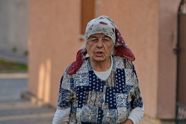 אשה אחת הולכת עם דלי תפוחי אדמה ליד בית הכנסת